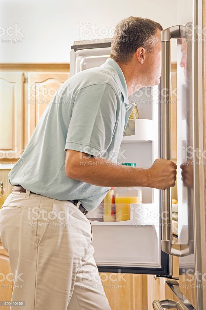 Man Standing in Front of Refrigerator in Kitchen stock photo