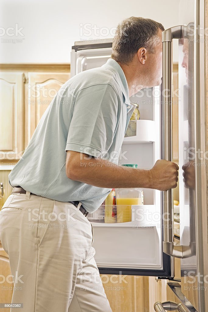 Man Standing in Front of Refrigerator in Kitchen royalty-free stock photo