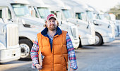 A mature man in h is 40s standing in front of a fleet of semi-trucks or tractor-trailers, holding a clipboard, with a serious, confident expression. He is an experienced truck driver or the owner of manager of a trucking company.