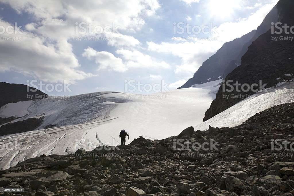 Man standing in front of the glacier Kebnepakteglaciären stock photo