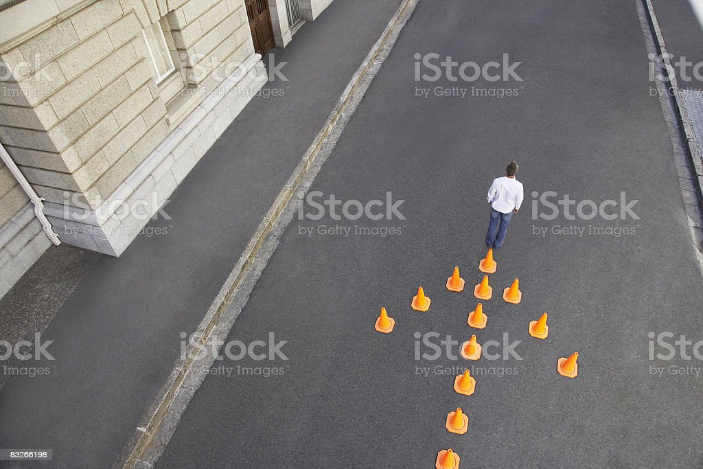 Man standing in front of traffic cones in arrow-shape royalty-free stock photo