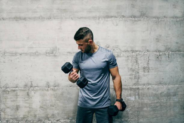 man står framför väggen och lyfta hantlar. hur många set är bra för biceps? - tyngdlyftning bildbanksfoton och bilder