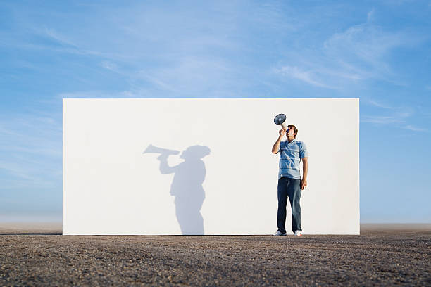 Man standing in front of wall outdoors with megaphone and shadow stock photo