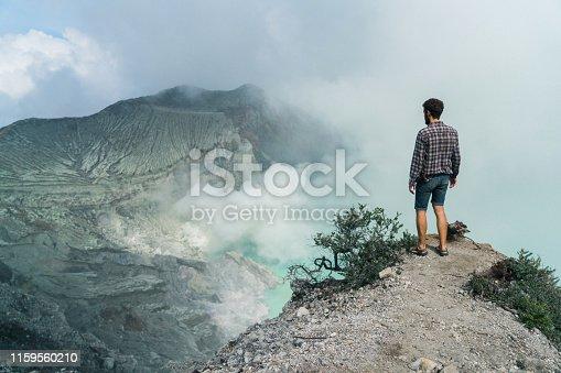 Man standing near Ijen volcano and sulphur minings, Java, Indonesia