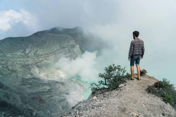 Man standing  in Ijen volcano and sulphur minings stock photo