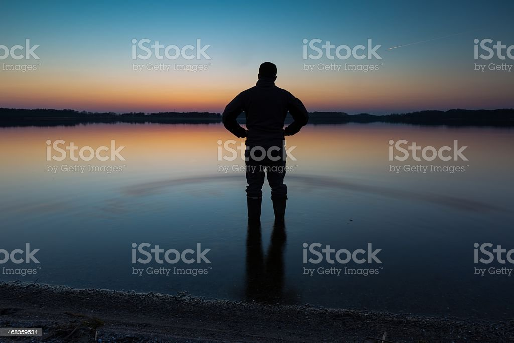 Man standing in lake water at sunset royalty-free stock photo