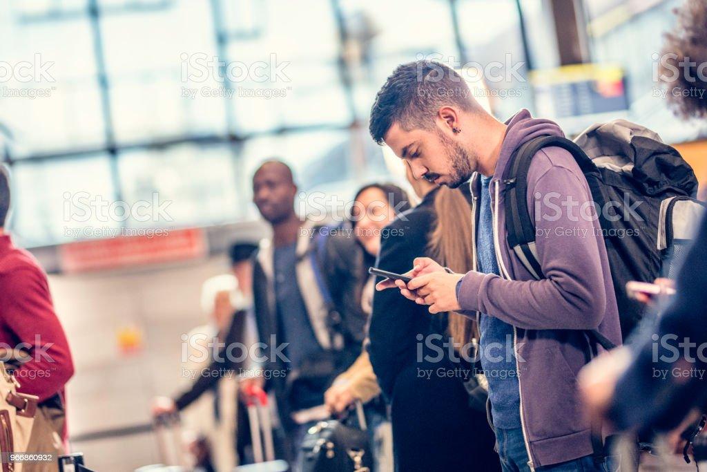 Mann Stand in der Schlange vor einem Flughafen mit einem Smartphone – Foto
