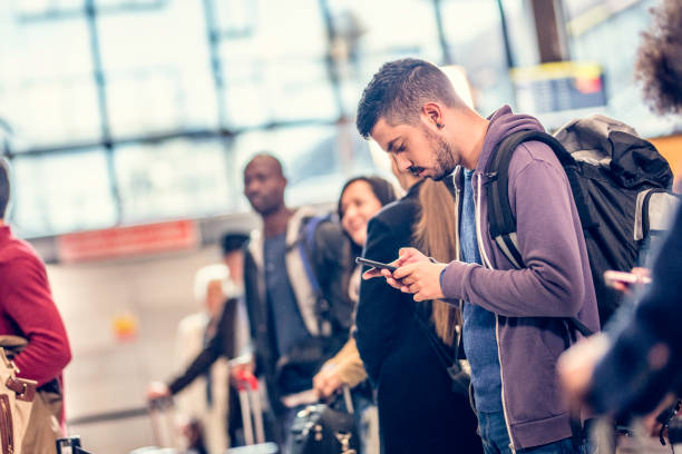 Man standing in line at an airport using a smart phone stock photo