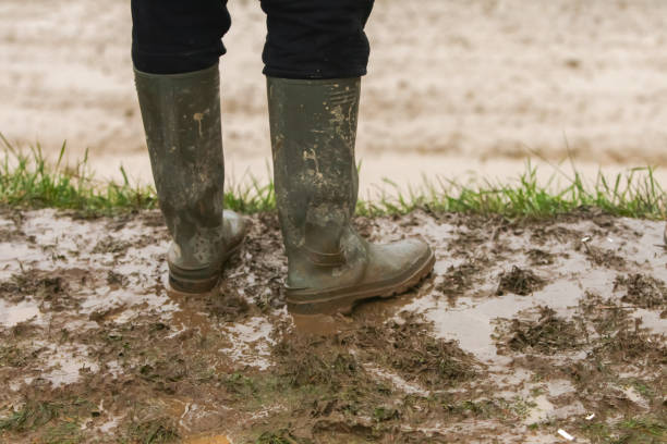 Man standing in mud A person in rubber boots standing in the mud. boot stock pictures, royalty-free photos & images