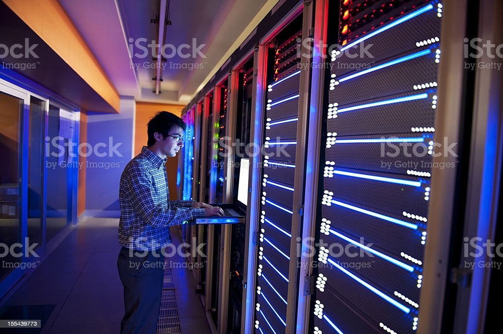 Man standing in neon light with IT servers stock photo