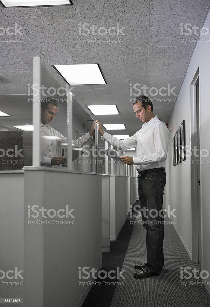 Mężczyzna stojący w korytarzu czytania Biuro zbiór zdjęć royalty-free