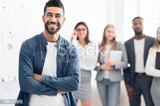 624700110istockphoto Man standing in office with colleagues on background 1084111574