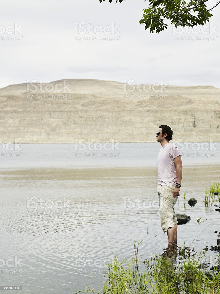 Man standing in river looking out zbiór zdjęć royalty-free