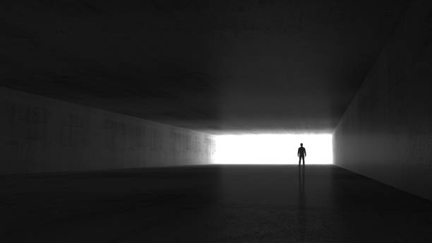 A man standing in the end of an empty dark tunnel stock photo