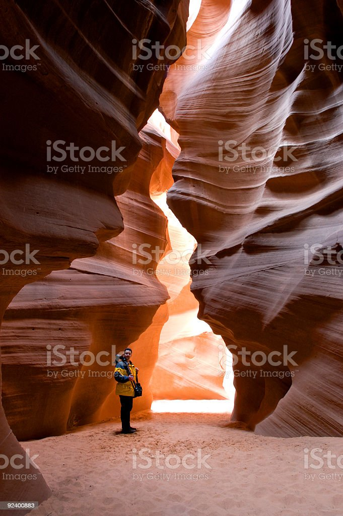 Man standing in the entrance to a slot canyon royalty-free stock photo