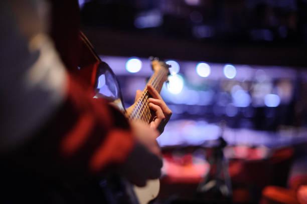 adam elinde bir gitar ile gece kulübünde ayakta - caz stok fotoğraflar ve resimler