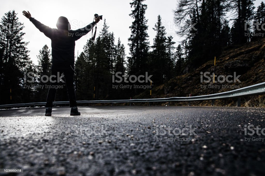 Man standing in the road - Winter scenery in mountain in the forest stock photo