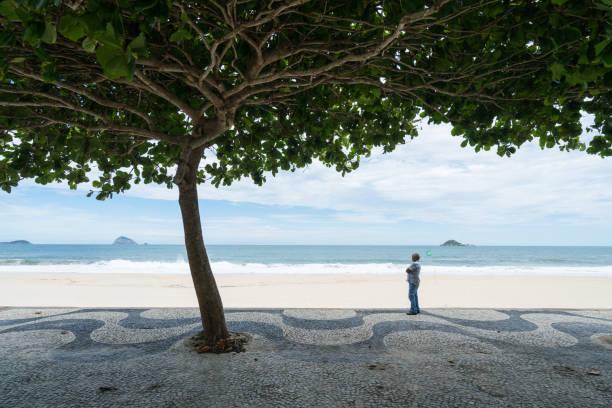 Mann steht im Schatten am Strand von San Conrado – Foto