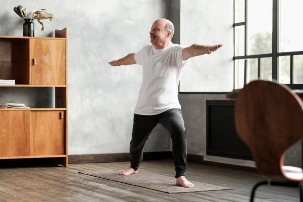 man standing in warrior two yoga pose practicing in living room stock photo