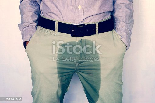 a dark spot on a light trousers. A man standing in wet pants against the wall. Urinary incontinence is an increasingly popular disease affecting younger males. incontinence and wet pants