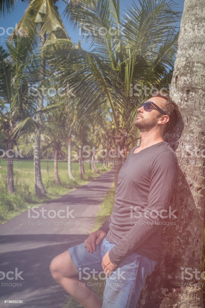 Man standing near empty road with palm trees. stock photo
