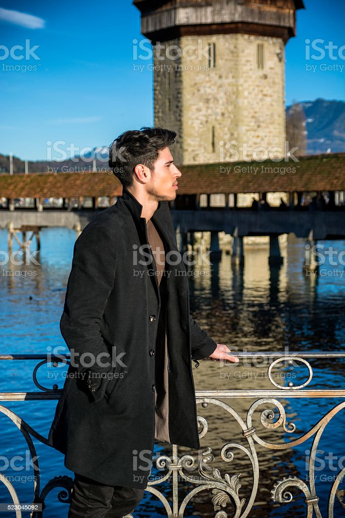 Man standing near metal fence in Lausanne stock photo
