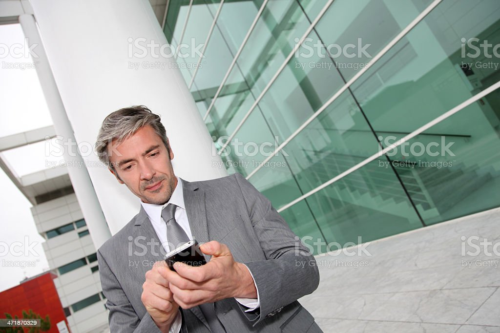 Man standing near modern building and sending a message royalty-free stock photo