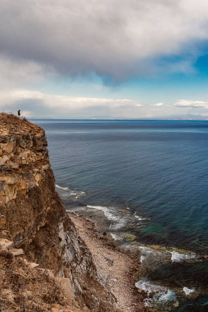 Man standing near the edge of the cliff with beautiful sea view stock photo