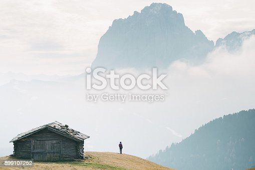 Silhouette of young Caucasian man standing near the hut with view of Dolomites mountains, Italy