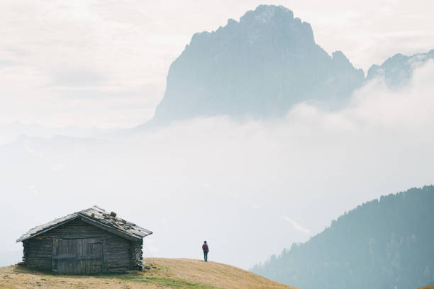 Man standing near the hut with view of Dolomites mountains, Italy stock photo