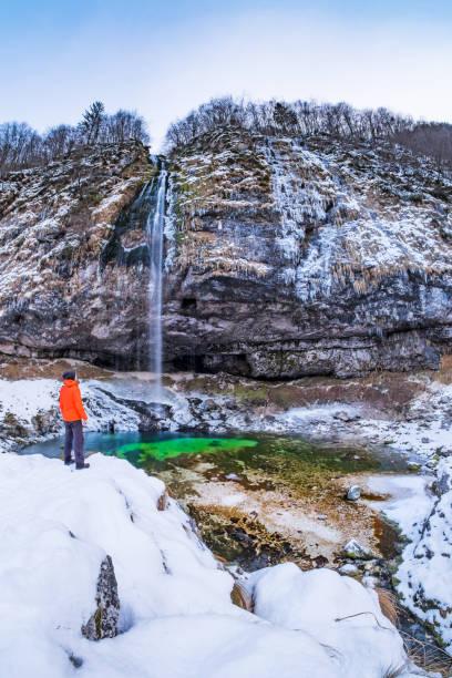 Mann steht in der Nähe von Wasserfall Goriuda im Schnee bedeckten Winterlandschaft – Foto