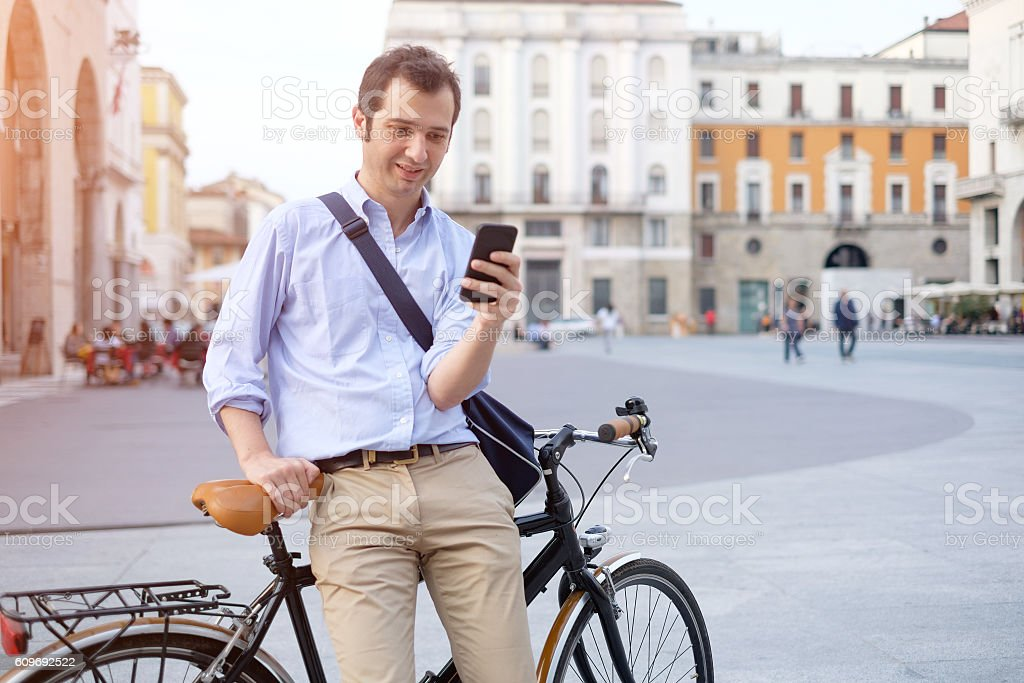 Man standing next to his bike hand holding mobile telephone - foto stock