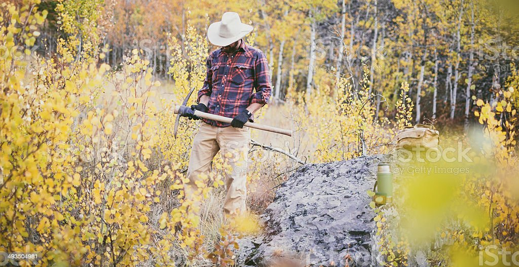 Man standing next to rock in the woods holding tool stock photo
