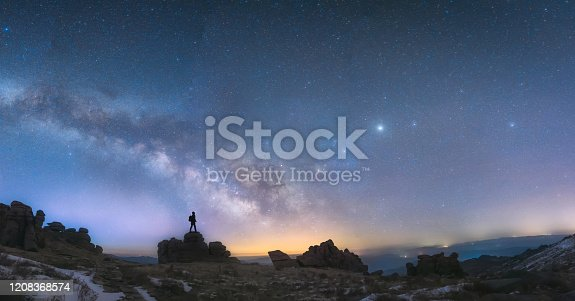 A man standing next to the Milky Way galaxy