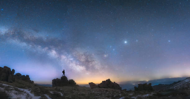 A man standing next to the Milky Way galaxy stock photo