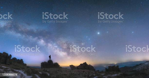 Photo of A man standing next to the Milky Way galaxy