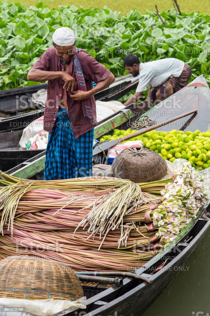 Barisal, Bangladesh - July 12, 2016: Man standing on a boat full of white water lilies and teasel gourd with his hand in his top pocket at the floating vegetable market stock photo