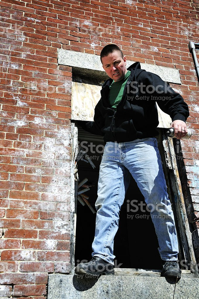 A man standing on a ledge holding a spray paint can. royalty-free stock photo