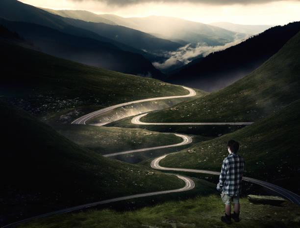 mann steht auf einem berggipfel bewundern die aussicht auf eine gekrümmte straße überqueren die berge. - detailliert stock-fotos und bilder