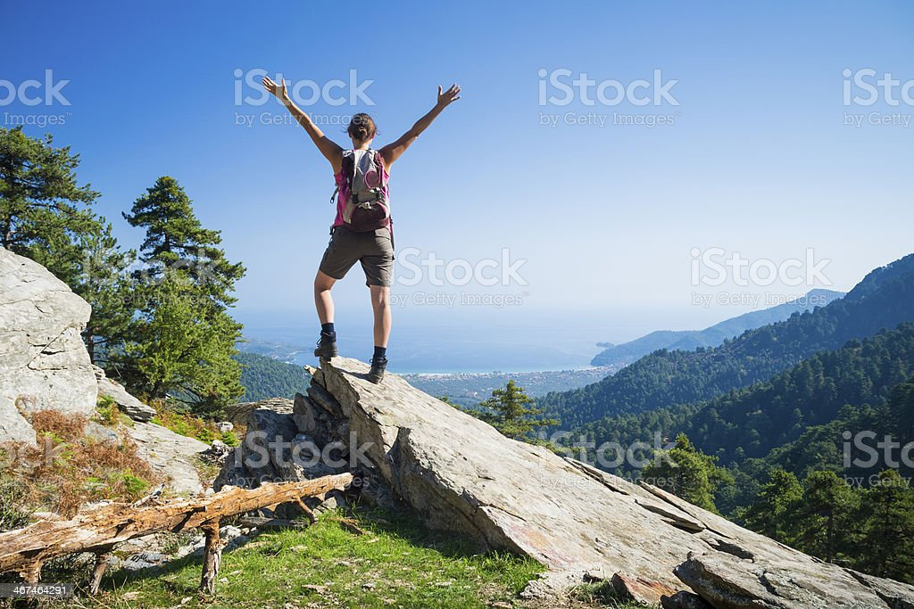 Man standing on a rock and enjoying the view stock photo