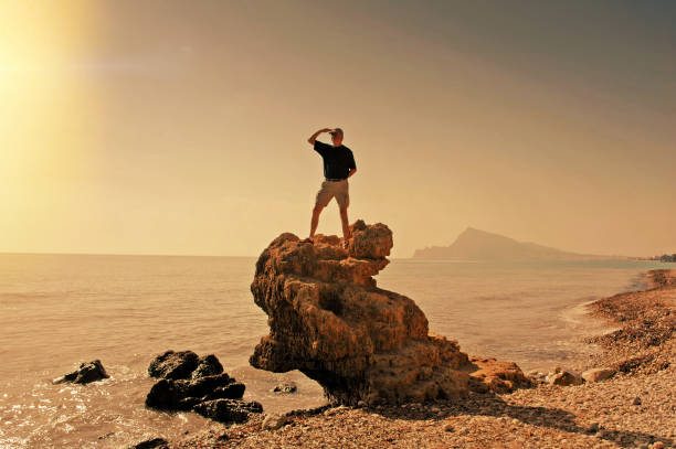 Man standing on a rock on the beach and looking at the distance,Spain stock photo