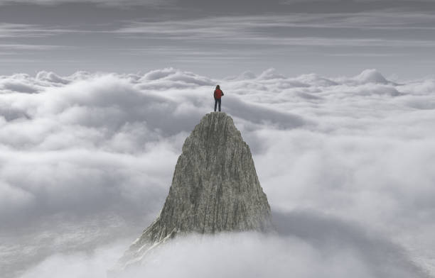 A man standing on a stone cliff over the clouds .Success concept. stock photo