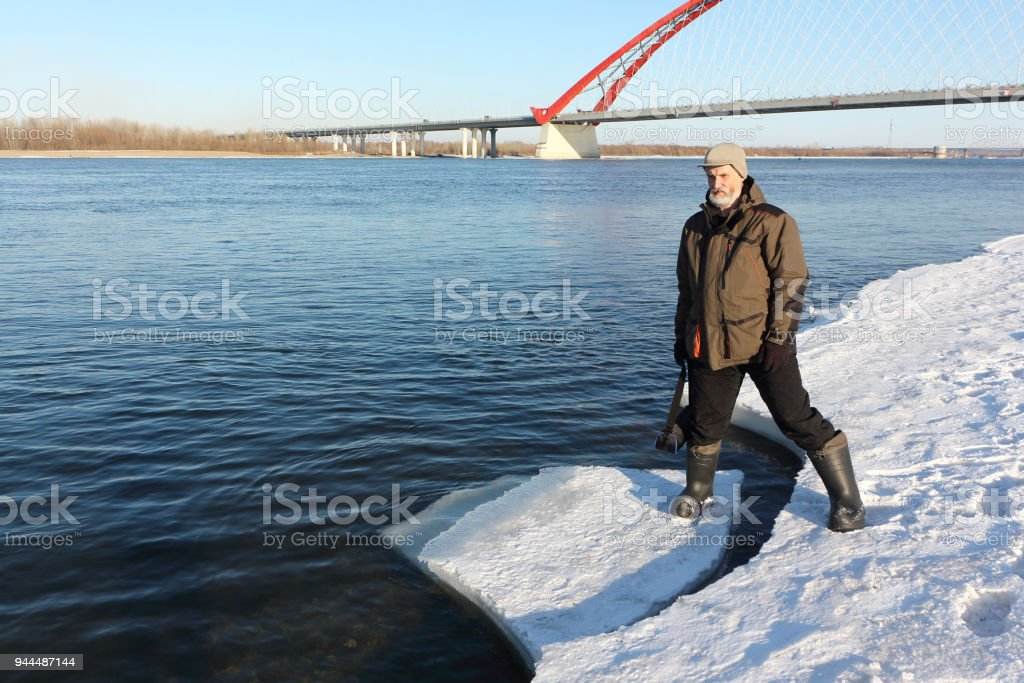 Man standing on an ice melting river, Ob River, Novosibirsk, Russia stock photo