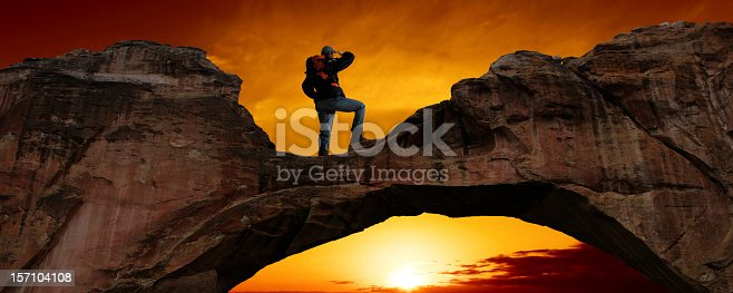 man with backpack standing on natural arch bridge at sunset, panoramic frame (XXXL)