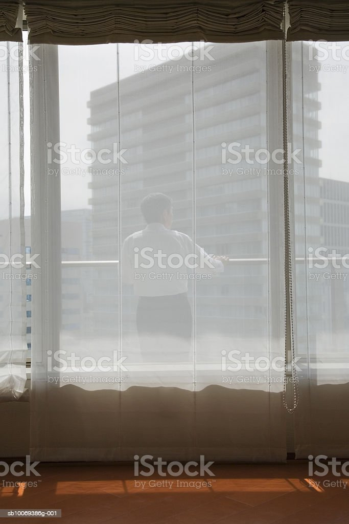 Man standing on balcony looking away, rear view royalty-free stock photo