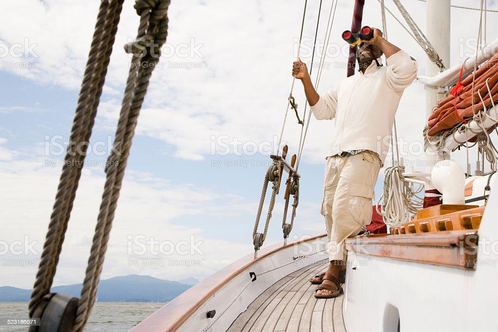 Man Standing on Boat Looking Through Binoculars stock photo