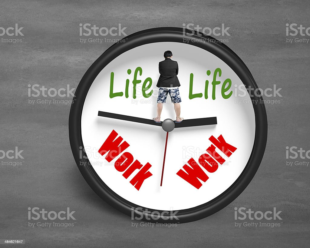 Man standing on clock hands with life and work face stock photo