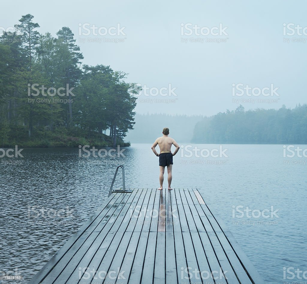 Man standing on end of swimming pier, rear view foto de stock royalty-free