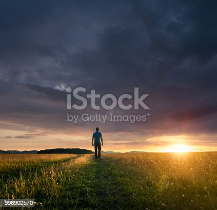 Man standing on meadow during a majestic sunset after a heavy rain