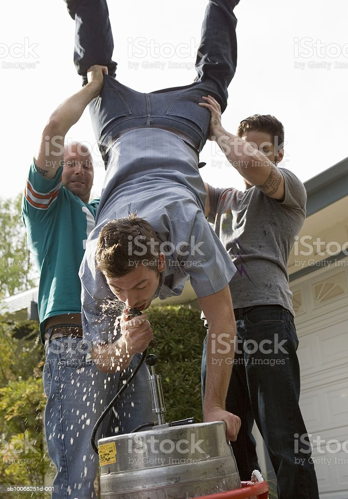 Man standing on hands on beer keg, being held by two friends royalty free stockfoto